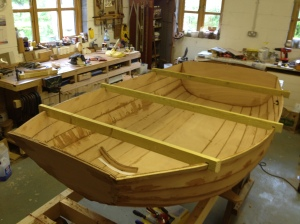 Scrap wood with slots to fit over the plank edges keeps the hull shape