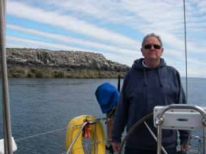 Tony, at our Farne anchorage. The cliff behind is covered in roosting birds.